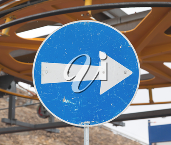 Blue road sign with white arrow pointing right, ski lift in Switzerland