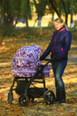woman with baby in perambulator walking in the autumn park