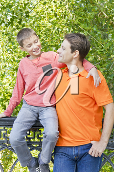 Father and son are talking smiling in summer park