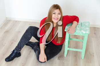 Horizontal attractive young girl with long brown healthy straight hair sitting on the floor