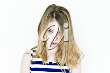 Cute teenager girl with blond long hair and big eyes on white wall in striped clothes