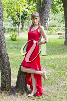 Beautiful lady in red are standing near tree summer day