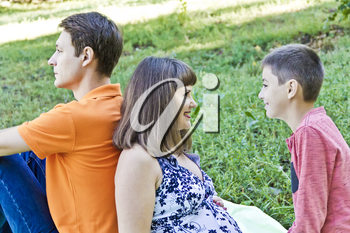 Happy family with pregnant mother are sitting on green grass