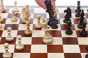 hand with black king beats white king on chessboard in chess game