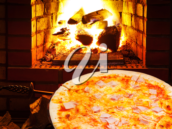 italian pizza with prosciutto cotto and open fire in wood burning oven