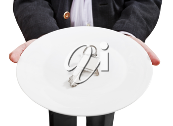 front view of businessman holds white plate with new door keys isolated on white background