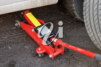 seasonal replacement of tires with jack outdoors - lifting car by jack