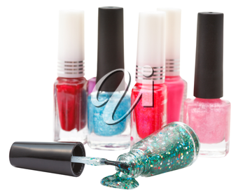 set of nail polish bottles and spilled green lacquer isolated on white