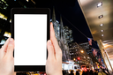 travel concept - tourist photograph New York avenue in night on tablet pc with cut out screen with blank place for advertising logo
