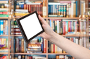 hand holds tablet pc with cut out screen and library on background
