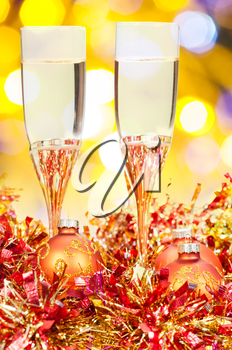 Christmas still life - two glasses of sparkling wine at golden and red Xmas decorations with yellow and violet blurred Christmas lights bokeh background