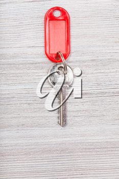 door key with red blank keychain on wood table