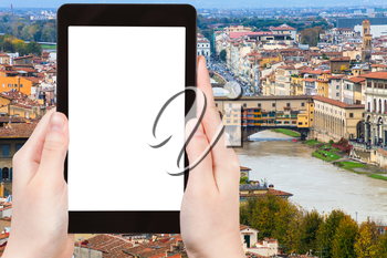 travel concept - tourist photographs ponte vecchio in Florence city on tablet with cut out screen with blank place for advertising in Italy