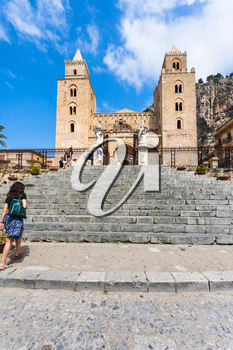 CEFALU, ITALY - JUNE 25, 2011: people near gate in Duomo di Cefalu in Sicily. Cathedral - Basilica of Cefalu was erected in 1131 in the Norman architectural style