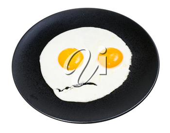 fried eggs on black plate isolated on white background. Fried eggs like the angry face