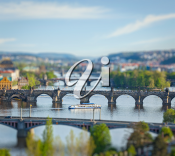 Travel Prague concept background - elevated view of bridges over Vltava river from Letna Park with tilt shift toy effect shallow depth of field. Prague, Czech Republic