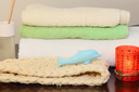 Towel stack, bast and soap in the form of a dolphin taken closeup.
