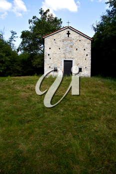italy  lombardy     in  the arsago seprio   old   church   closed brick tower      wall grass