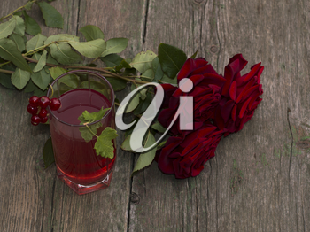 bouquet of beautiful roses and glass of juice of red color, festive card on a subject flowers