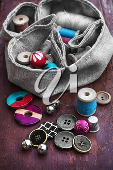 set of threads and buttons on old wooden background