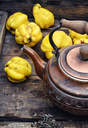 Obsolete wooden box with a stylish copper kettle and fruit quince