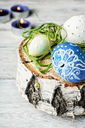 Decorated with painted Easter eggs on birch slice on light background