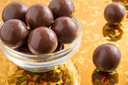 Round chocolate candy in small glass cup on colorful background close-up
