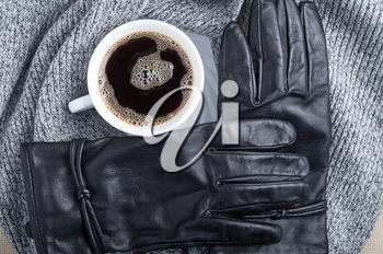 Top view of a white cup of coffee, a gray woolen scarf and black women's gloves are made of leather