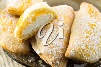 Sweet pies with curd sprinkled with powdered sugar on a dark plate with shallow depth of field