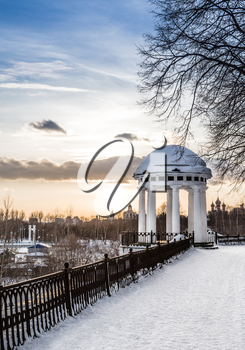 Arbor on the quay in the heart of city. Spring snowy evening. Russia, Yaroslavl.