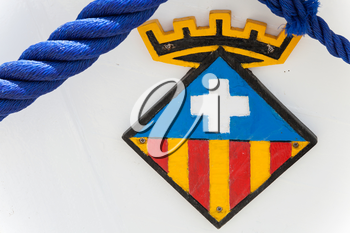 Calafell, Spain - August 13, 2014: Calafell town Coat of arms on the bow of white fishing boat,  Catalonia, Tarragona region, Spain