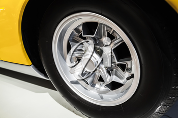 Chromed wheel disc. Yellow luxury Italian vintage sport car fragment, close up photo with selective soft focus
