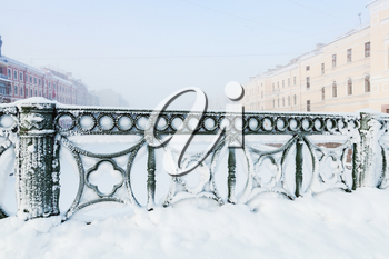 Forged green fence of Mogilev bridge covered with snow, Griboedov canal, Saint Petersburg, Russia