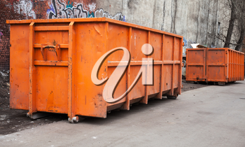 Big metal orange trash containers in the city