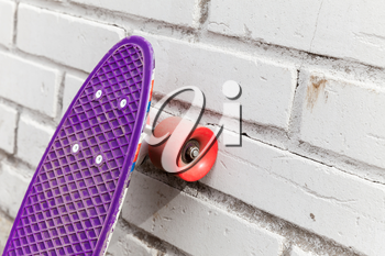 Modern purple skateboard stands near white brick wall, close-up fragment