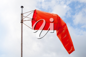 Windsock. Red wind indicator over blue cloudy sky