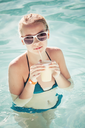 Little blond girl drinks cocktail in swimming pool, vintage toned photo filter effect