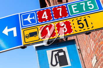 Colorful road signs with route numbers, turn arrow and gas station icon