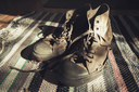 Old sneakers stand on striped knitted carpet. Retro stylized photo with tonal correction filter effect, old style