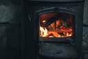 Fire burning in black iron stove. Closeup photo with selective focus