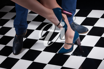 Woman's and man's legs in dancing poses on a checkered background