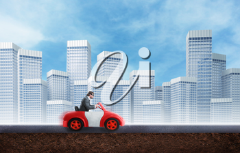 Young businessman driving a toy car agaist the city