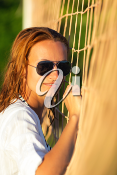 Portrait of attractive woman near volleyball net on the beach
