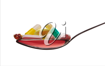 Spoon full of various pills. Isolated on white