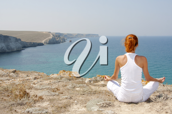 Woman in white meditating in mountains against the sea