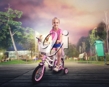 Smiling little girl cycling on pink bike on the street in the night