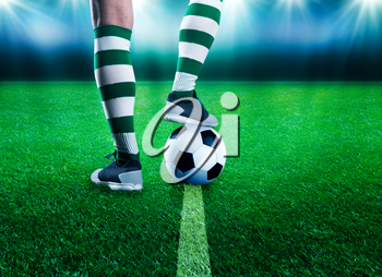 Football player legs with a ball standing on the stadium