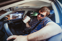 Man speaking on the phone in the car and drinking coffee