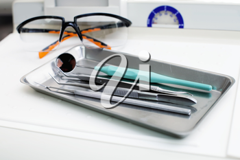 Dentist instruments and protective eyeglasses on the table
