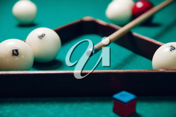 Billiard items on the table: balls, chalk, stick and triangle